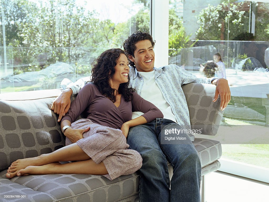Couple embracing on sofa, smiling