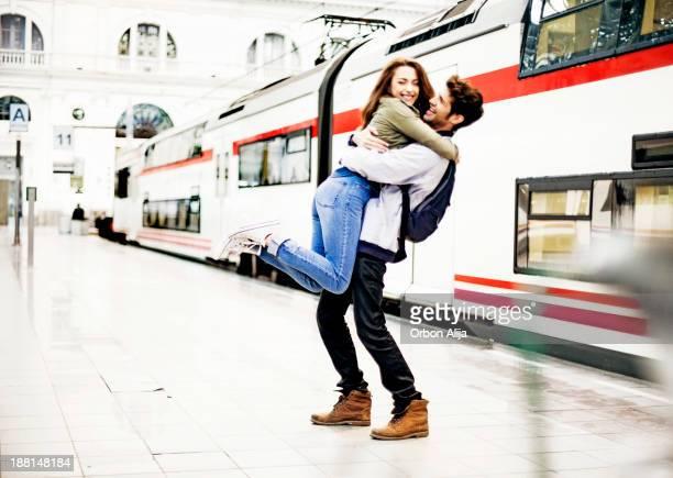 Couple embracing on station platform