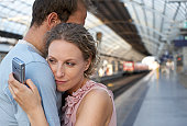Couple embracing on station platform, woman looking at mobile phone