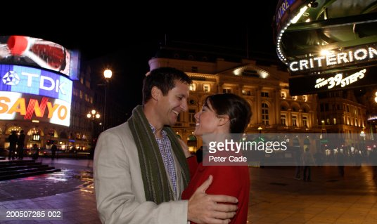 Couple embracing on street, smiling, side view, night : Stock Photo