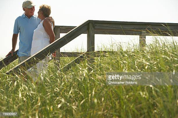 Couple embracing on wooden path in grassy field