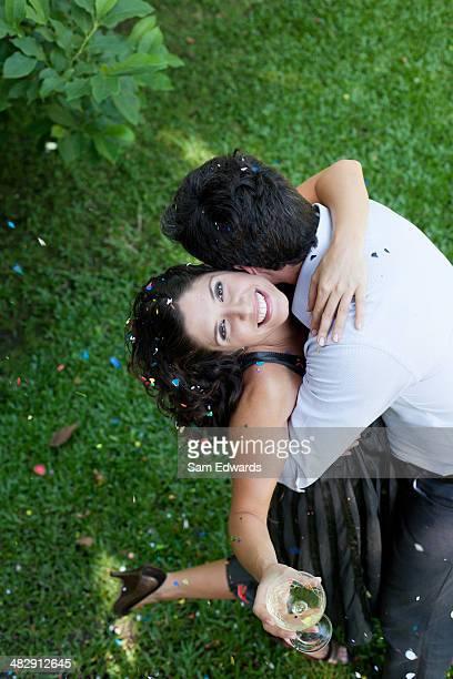 Paar umarmen im Freien mit Weißwein und Konfetti Lächeln