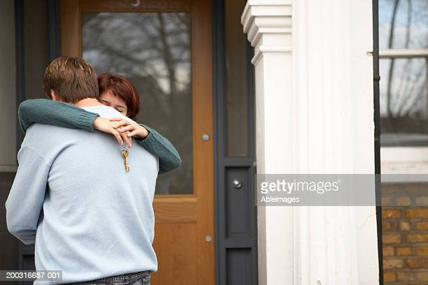 Couple embracing outside front door