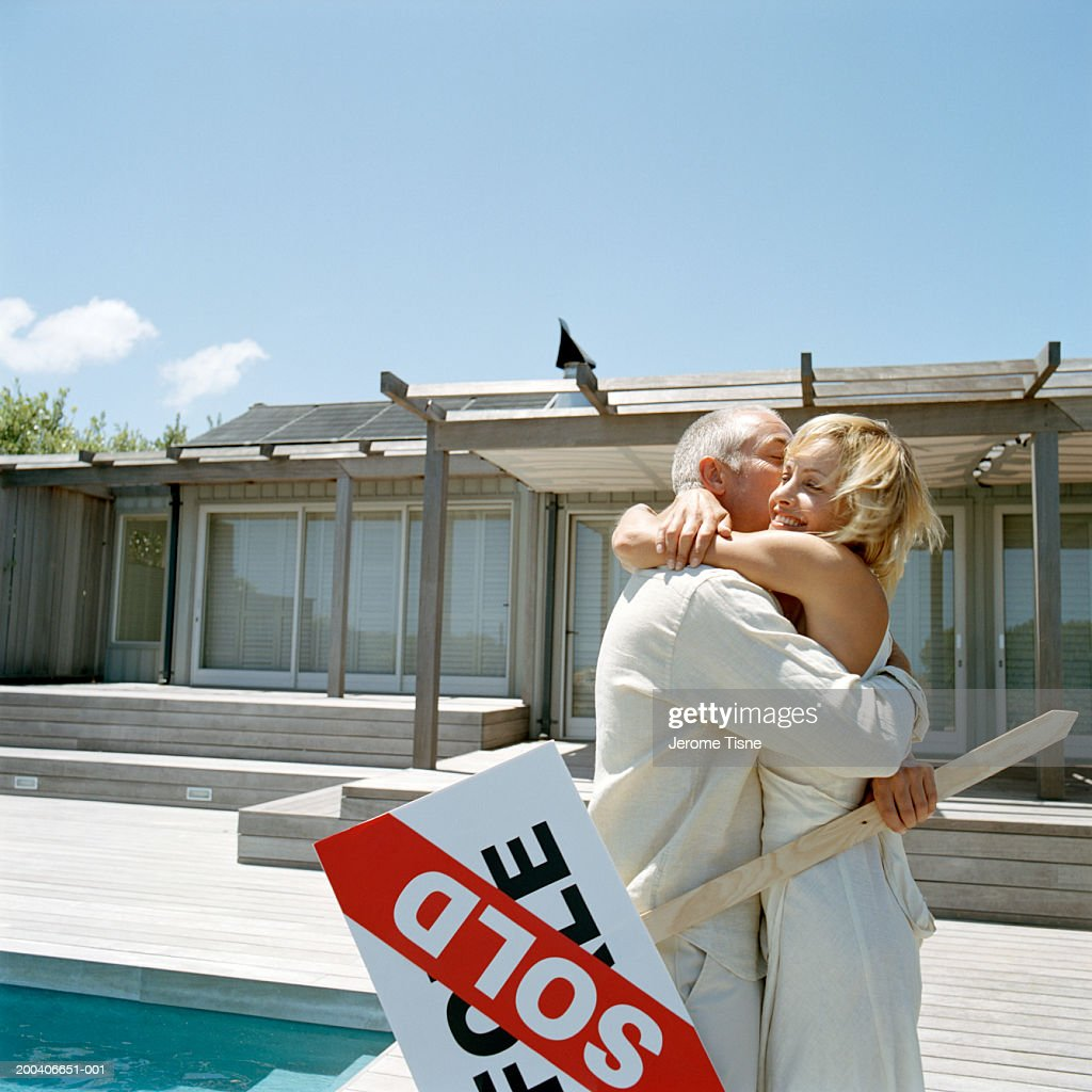 Couple embracing outside home, holding 'Sold' sign : Stock Photo