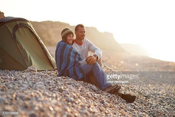 Couple embracing outside tent on pebble beach.