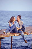 Couple embracing, sitting on jetty