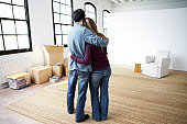 Couple embracing, standing indoors, rear view