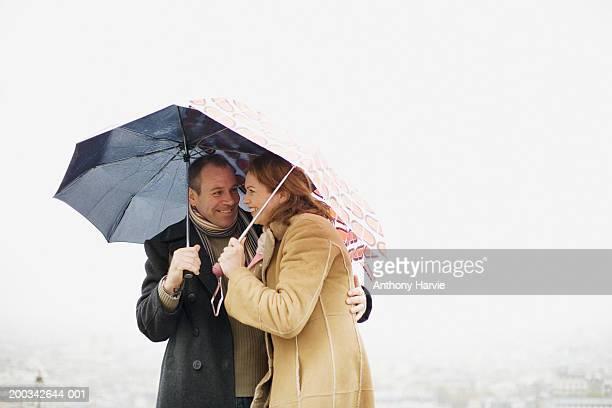Couple embracing under umbrellas, smiling