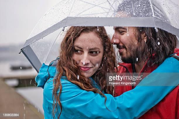 couple embracing underneath umbrella