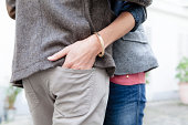 Couple embracing, woman placing hand in man's pant seat pocket