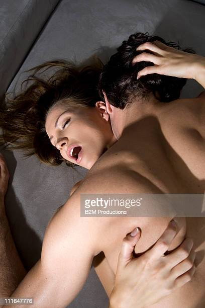 Couple engaged in sexual intercourse on sofa