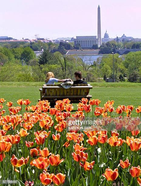 A couple enjoy a warm Spring day 26 April in Arlington Virginia overlooking Washington DC The designer of the US capital Frenchborn Pierre L'Enfant...