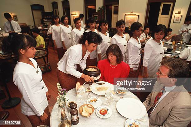 A couple enjoy the culinary delights of 'Rijstaffel' an Indonesian meal of a variety of dishes that is traditionally served by numerous waitresses or...