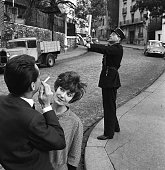 A couple enjoy the sights in Paris whilst a gendarme goes about his business behind them 31st October 1960