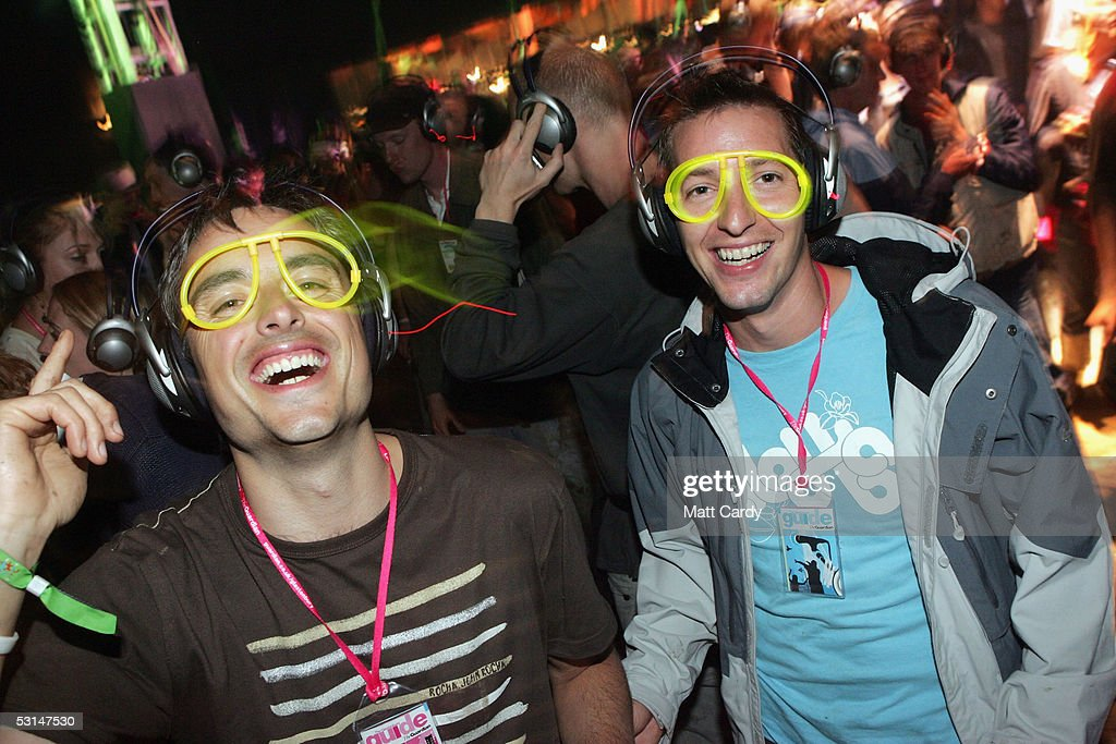 A couple enjoy the silent all-night disco in the Dance Tent on the second day of the Glastonbury Music Festival 2005 at Worthy Farm, Pilton on June 25, 2005 in Somerset, England. The headphones cost ?75, have two channels and over a 1000 were given out. The festival runs until June 26.