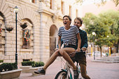 Couple enjoying on a bicycle in the city. Cheerful woman sitting on handlebar of boyfriends bicycle.
