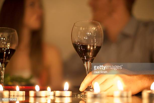 Couple enjoying a glass of red wine by candlelight
