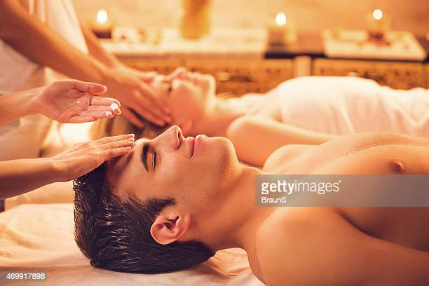 Couple enjoying at the spa while receiving facial massage.