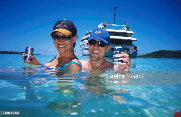 Couple enjoying beer in lagoon, Blue Lagoon cruise, Nanuya Lailai Island.