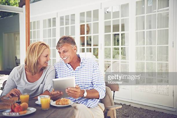 Couple enjoying breakfast while using a tablet