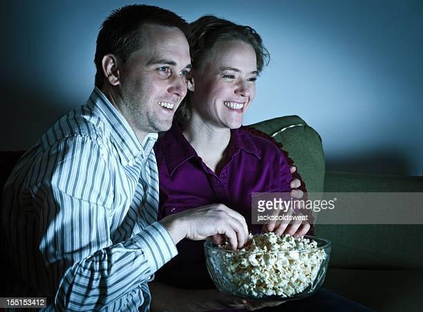 Couple enjoying date night in, watching a movie