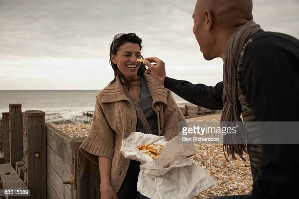 Couple enjoying fish 'n' chips on the beach