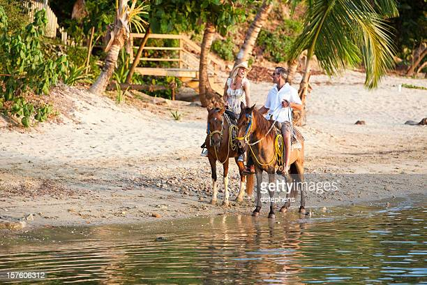 Couple enjoying horseback ride on the beach