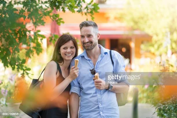 Couple enjoying ice cream in city street