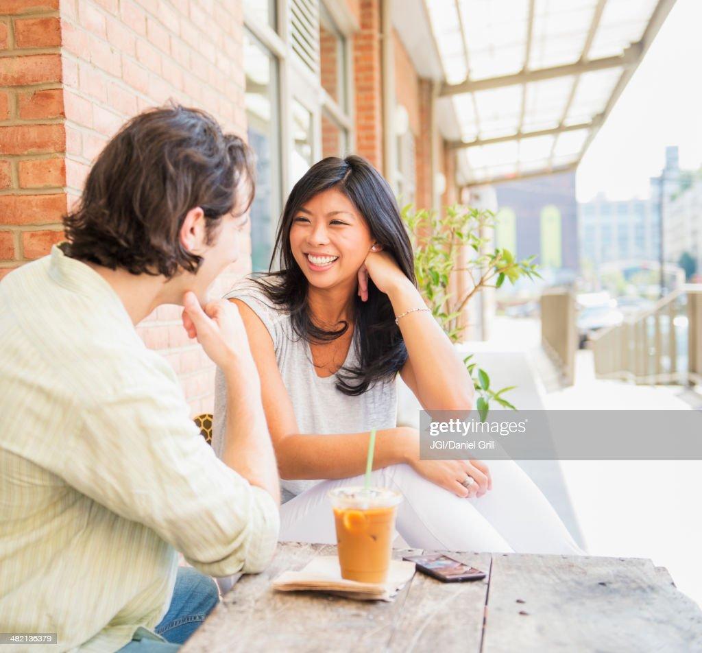 Couple enjoying iced coffee at sidewalk cafe : Stock Photo