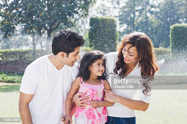 Couple enjoying in front of a sprinkler with their daughter, Gurgaon, Haryana, India