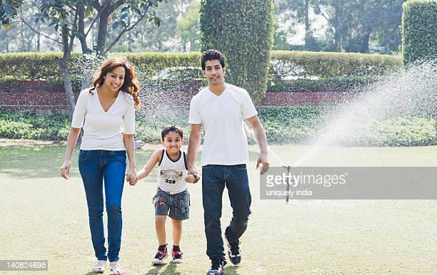 Couple enjoying in front of a sprinkler with their son, Gurgaon, Haryana, India