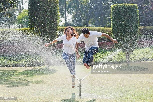 Couple enjoying near a sprinkler, Gurgaon, Haryana, India