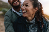 Smiling asian woman being embraced by her boyfriend from behind. Couple enjoying on vacation.
