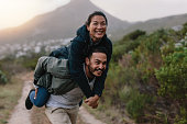 Handsome young man carrying his girlfriend on back. Couple enjoying piggyback ride in countryside.