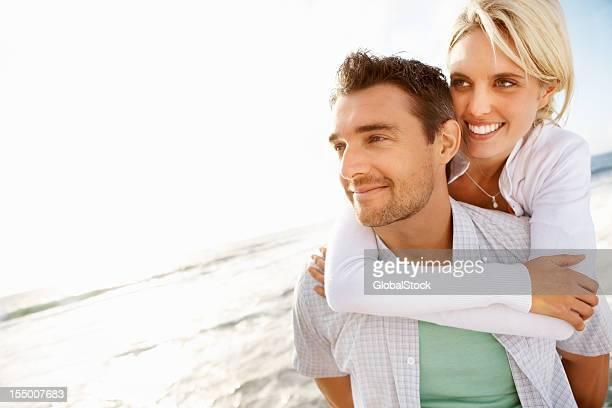Couple enjoying piggyback ride on the beach