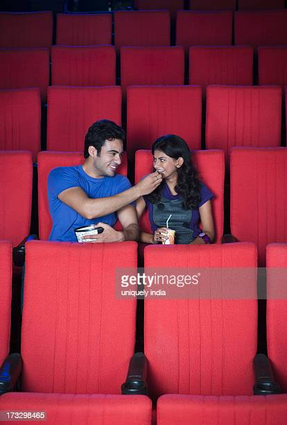 Couple enjoying popcorns while watching movie in a cinema hall