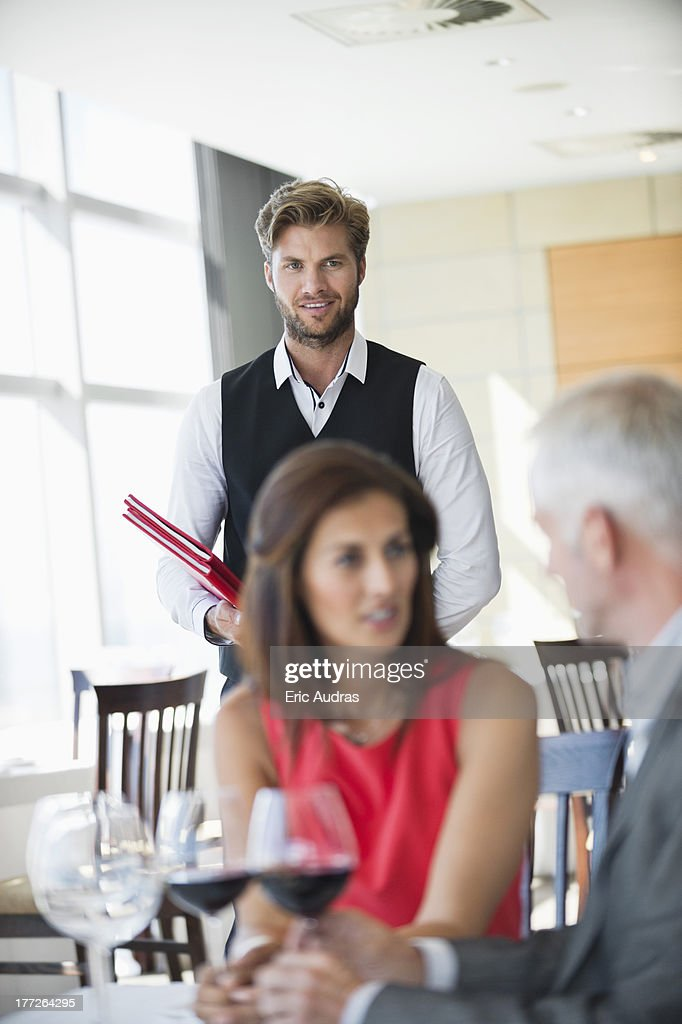 Couple enjoying red wine in a restaurant with waiter in the background : Stock Photo