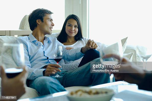 Couple enjoying red wine with friends