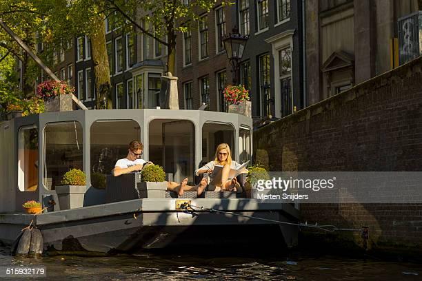 Couple enjoying sunshine on houseboat rear