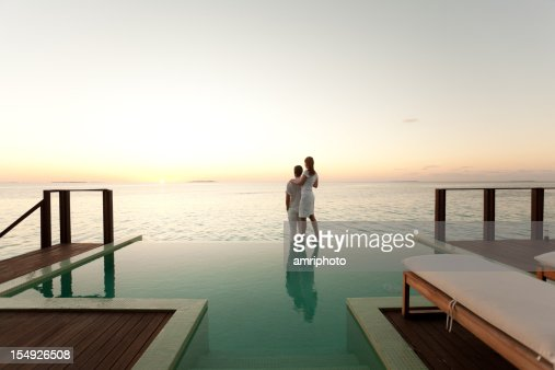 Couple enjoying the sunset at poolside