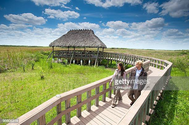 A couple enjoys a stroll along a wooden walkway in the Everglades National Park, Florida.