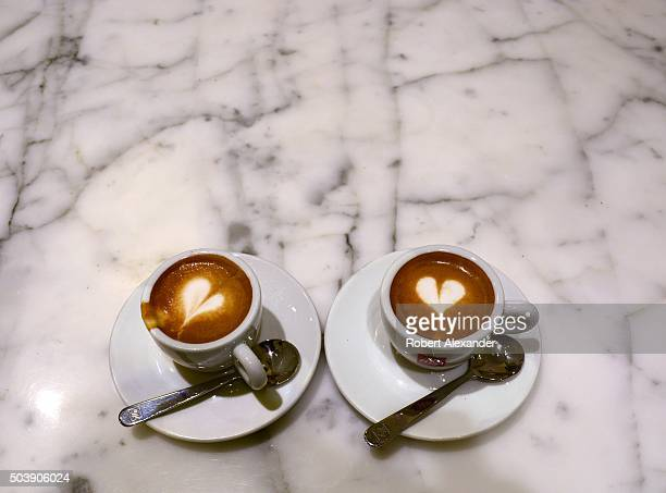 A couple enjoys cups of caffe' macchiato sometimes called espresso macchiato at a sidewalk cafe in Florence Italy