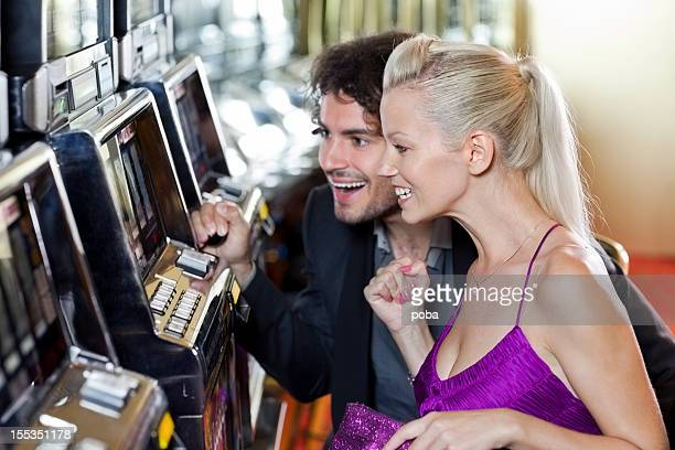 couple enjoys gambling in the casino on slot machines