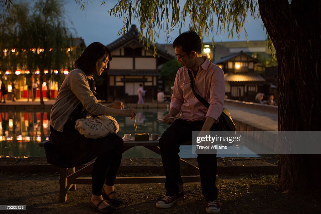 A couple enjoys sake and local foods during the Uzumasa Edosakaba, an event recreating an edo-period bar at the Toei Kyoto Studio Park on May 30, 2015 in Kyoto, Japan. The Toei Kyoto Studio Park, a studio park built next to a working film set, turned itself into a big edo-period bar where people can drink and enjoy edo period culture including Japanese cuisine and samurai sword fighting.