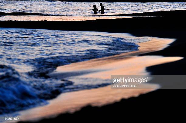 A couple enjoys the sea during the sunset at Legrena beach some 60 kilometers south of Athens on July 23 2011 AFP PHOTO / ARIS MESSINIS