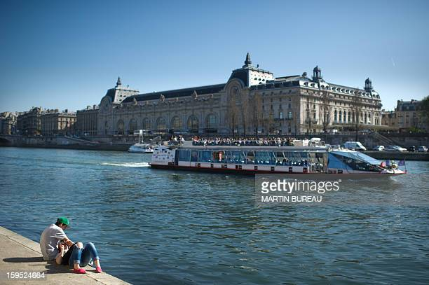 A couple enjoys the sun along the river Seine on March 26 2012 in Paris AFP PHOTO / MARTIN BUREAU