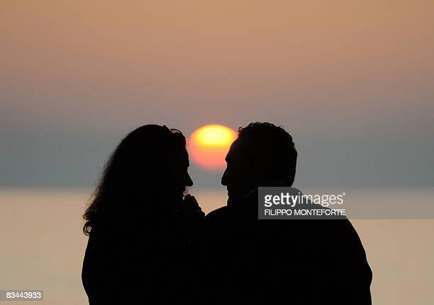 A couple enjoys the sunset on Bibbiona beach near La California where the 'American elections for non Americans' take place in the Livorno region of...