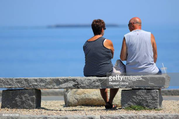 A couple enjoys the view of the ocean from a bench on Bearskin Neck in Rockport Mass July 31 2017