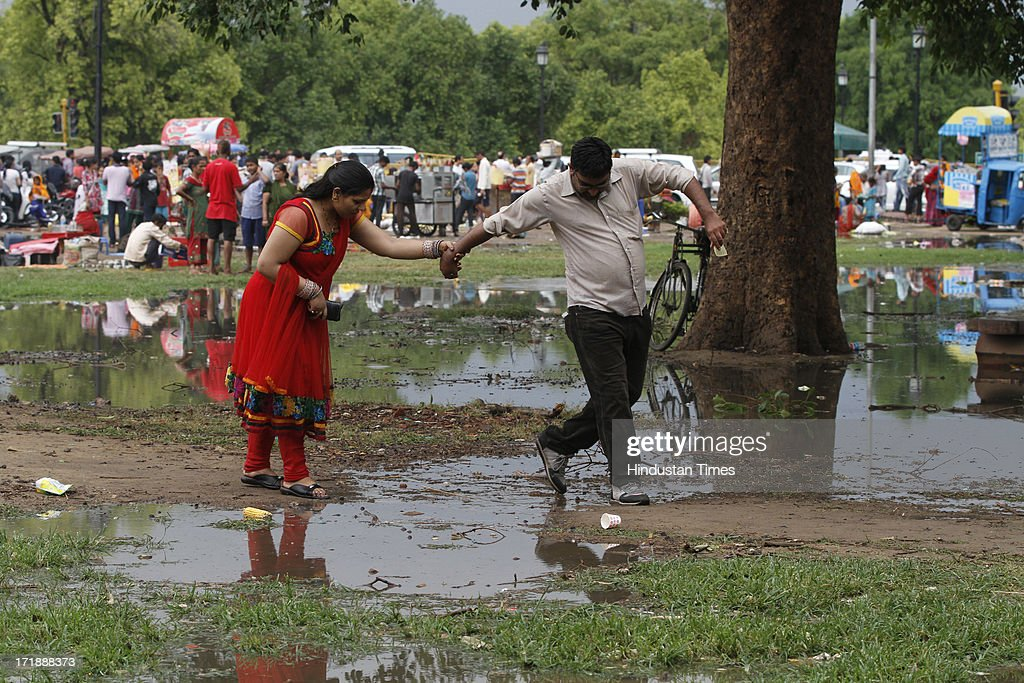 A couple enjoys weather turns pleasant at India Gate lawn, following rain on June 29, 2013 in New Delhi, India. Weather department forecast the country will receive normal rains this year, raising prospects of a stronger performance by Asia's third-largest economy.