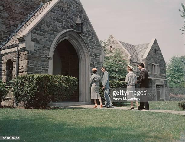Couple Entering In Church Each Carrying Bible